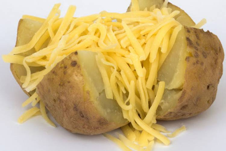 A large oven baked potato topped with grated mild cheddar cheese.